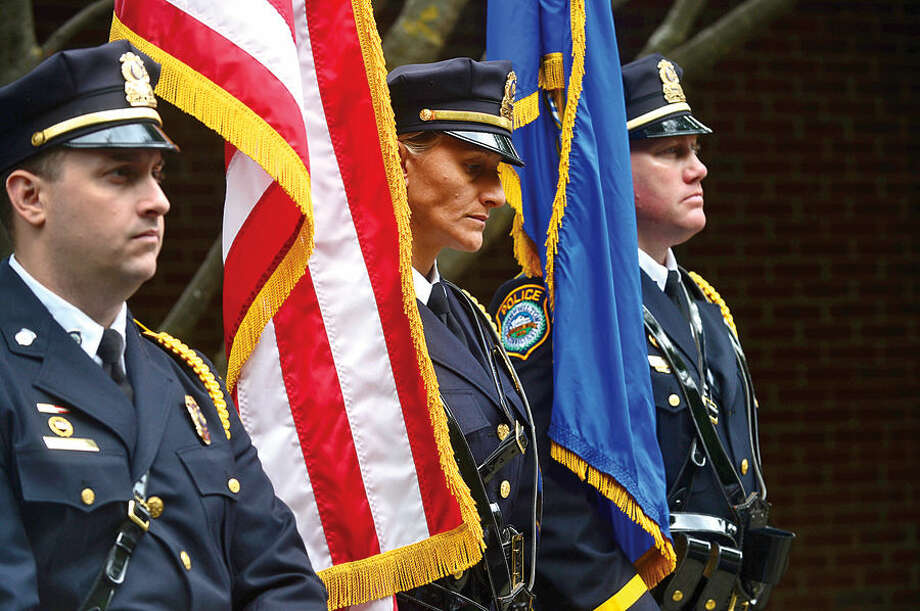 Hour photo / Erik Trautmann Wilton Police Honor Guard, Officer Tim Fridinger, Detective Eva Zimnoch, and Officer Michael Tyler, listen to the invocation during Wilton's September 11th memorial service Friday at Fire Department Headquarters.
