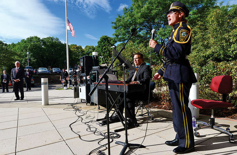 Hour photo / Erik Trautmann Norwalk Police Detective Kristina Lapak and accompanist David harris sing God Bless America as Norwalk holds their annual 9-11 Remembrance ceremony in the plaza at the front entrance of City Hall Friday.
