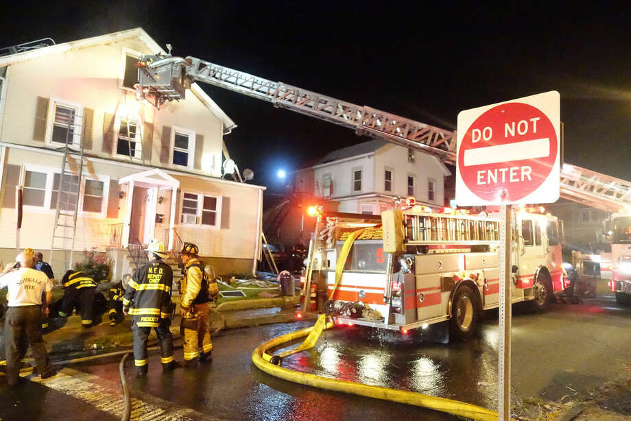 Hour photo/Jeff Dale Fire crews battle a 20 Larsen St. fire Monday night.