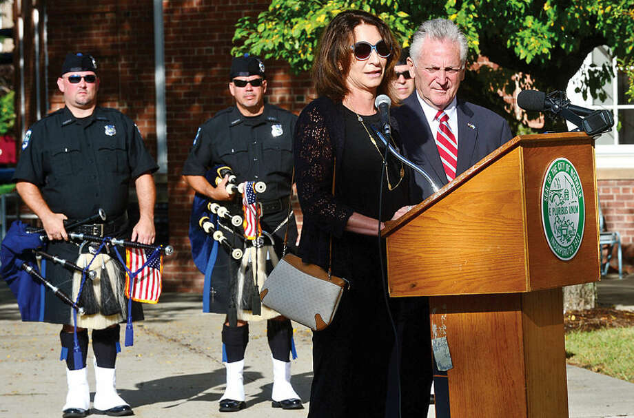 Hour photo / Erik Trautmann Director Norwalk Parking Authority, Kathryn Hebert, reads the name of her brother, a victim of the Setember 11 attacks, as Norwalk holds their annual 9-11 Remembrance ceremony in the plaza at the front entrance of City Hall Friday.