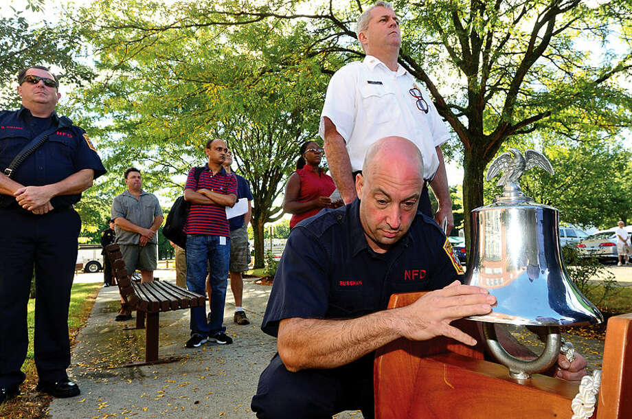 Hour photo / Erik Trautmann Firefighter Adam Sussman tolls the bell for the Norwalk resident who were victms of the Setember 11th attacks as Norwalk holds the annual 9-11 Remembrance in the plaza at the front entrance of City Hall Friday.