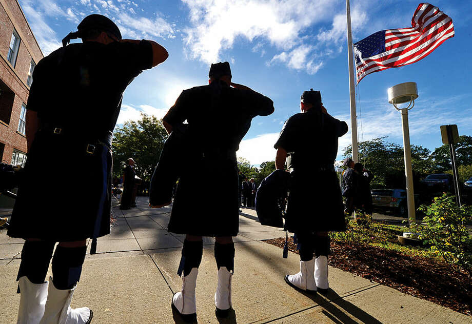 Hour photo / Erik Trautmann The Fairfield County Police Pipe Band salute the flag as Norwalk holds the annual 9-11 Remembrance in the plaza at the front entrance of City Hall Friday.