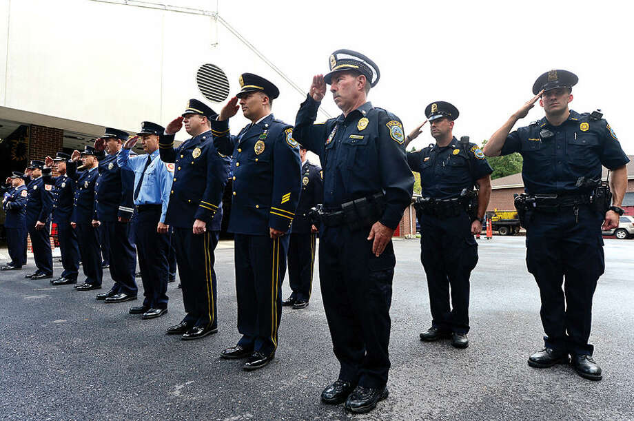 Hour photo / Erik Trautmann Wilton Police and Fire Department personnel salute during Wilton's September 11th memorial service Friday at Fire Department Headquarters.