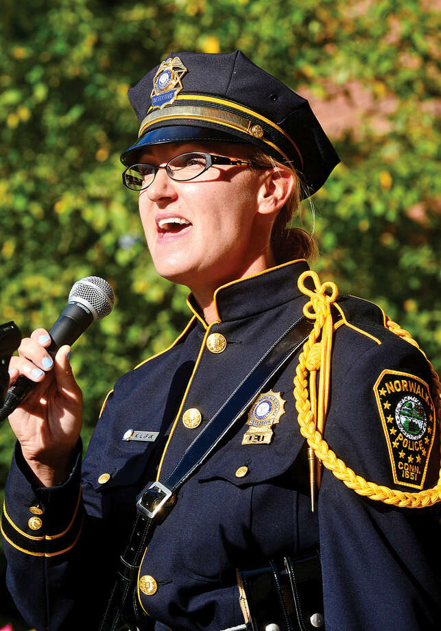 Hour photo / Erik Trautmann Norwalk Police Detective Kristina Lapak sings the National Anthem as Norwalk holds their annual 9-11 Remembrance ceremony in the plaza at the front entrance of City Hall Friday.