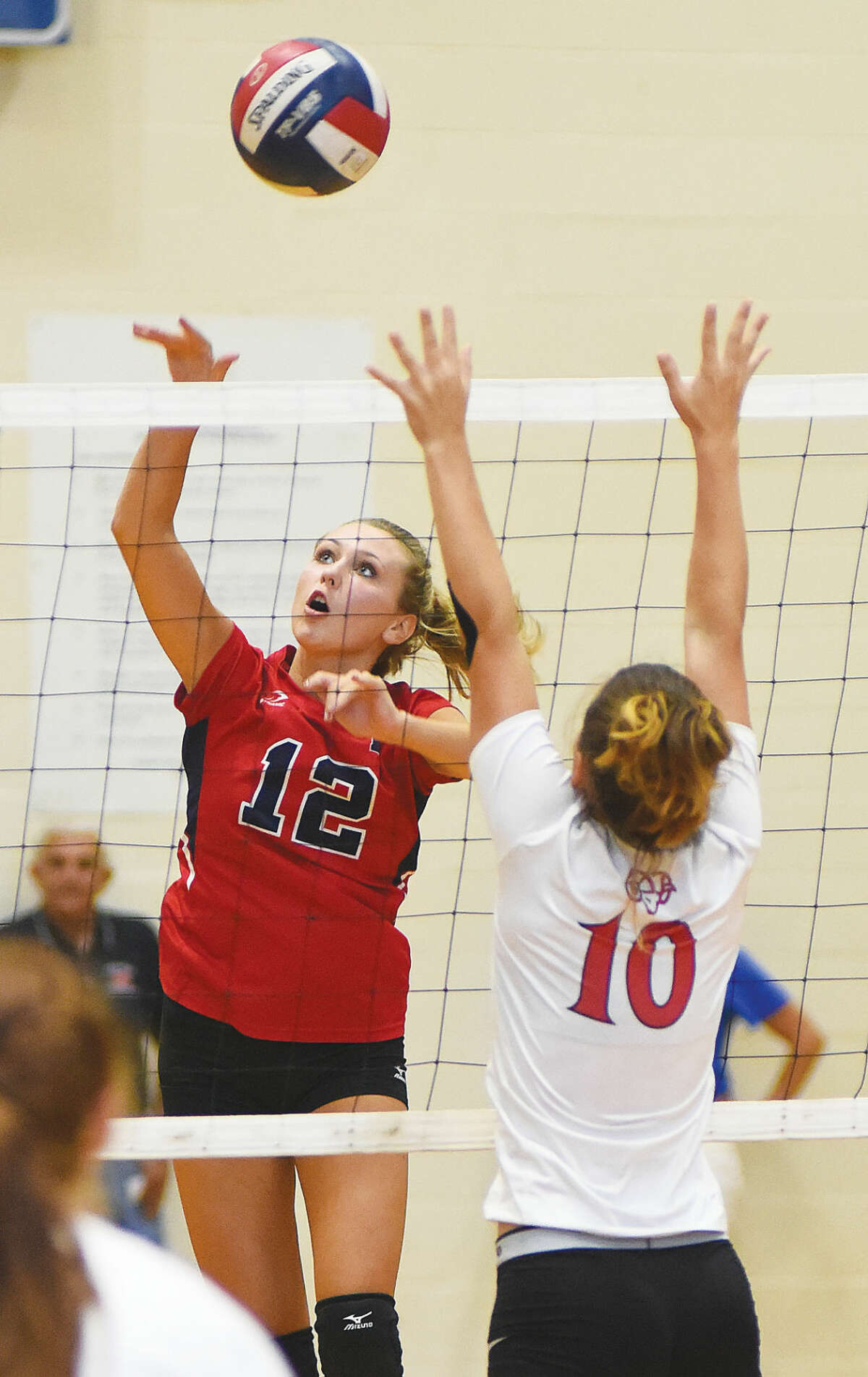 Hour photo/John Nash - McMahon's Taylor Morton (12) spikes the ball over the outstretched arms of New Canaan's Sara Brindisi during Friday's season-opening game in Norwalk. McMahon 3-0.