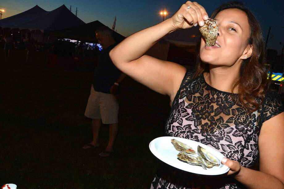 Hour Photo/Alex von Kleydorff Vanessa Peterson enjoys the oysters from Flotilla 72 at the Norwalk Seaport Association Oyster Festival that started on Friday