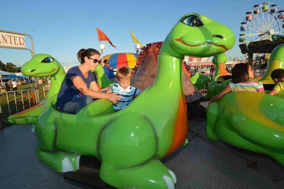 Hour Photo/Alex von Kleydorff Douglas Hamilton rides the dinosaur with mom Andrea at The Oyster fest Friday night