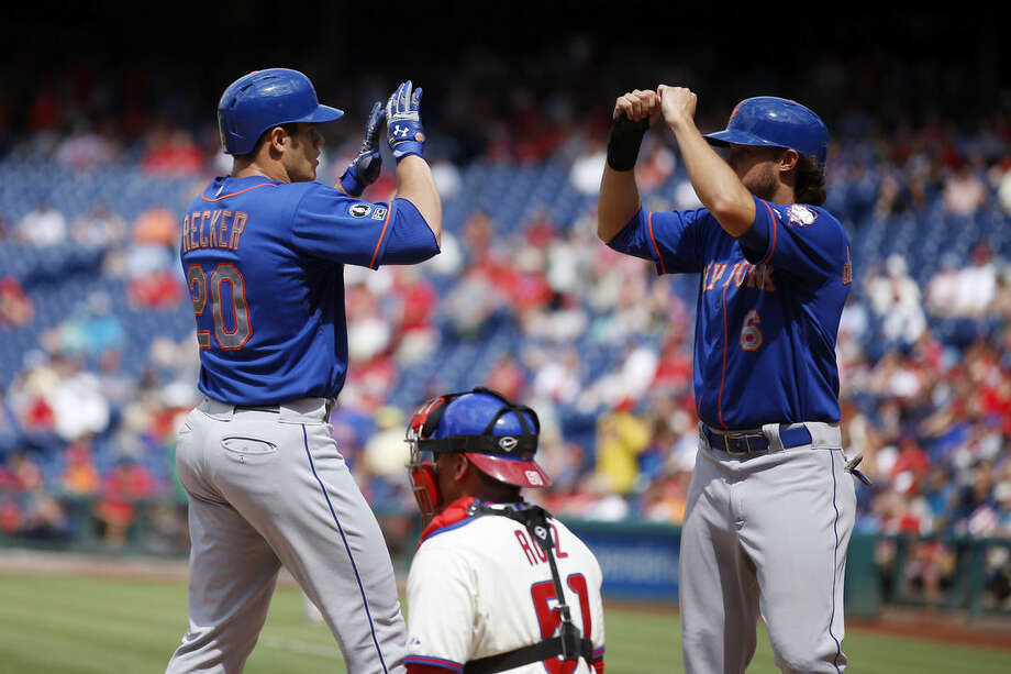 New York Mets' Anthony Recker, left, and Matt den Dekker, right, celebrate over Philadelphia Phillies catcher Carlos Ruiz after Recker's three-run home run during the seventh inning of a baseball game, Monday, Aug. 11, 2014, in Philadelphia. New York won 5-3. (AP Photo/Matt Slocum)