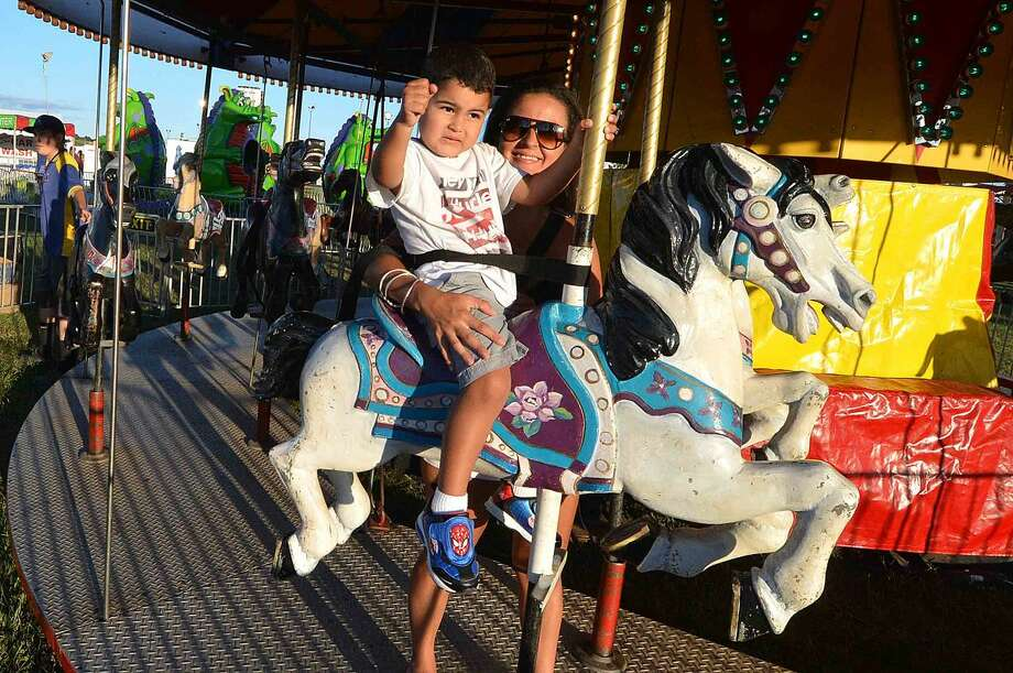 Hour Photo/Alex von Kleydorff Maria and son Brandon Duran ride the Carousel at The Oyster fest