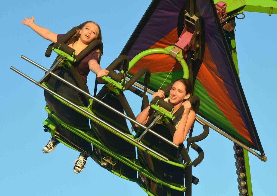 Hour Photo/Alex von Kleydorff Maya Goosman and Julianna Dimeglio ride The Cliffhanger at The Oyster fest