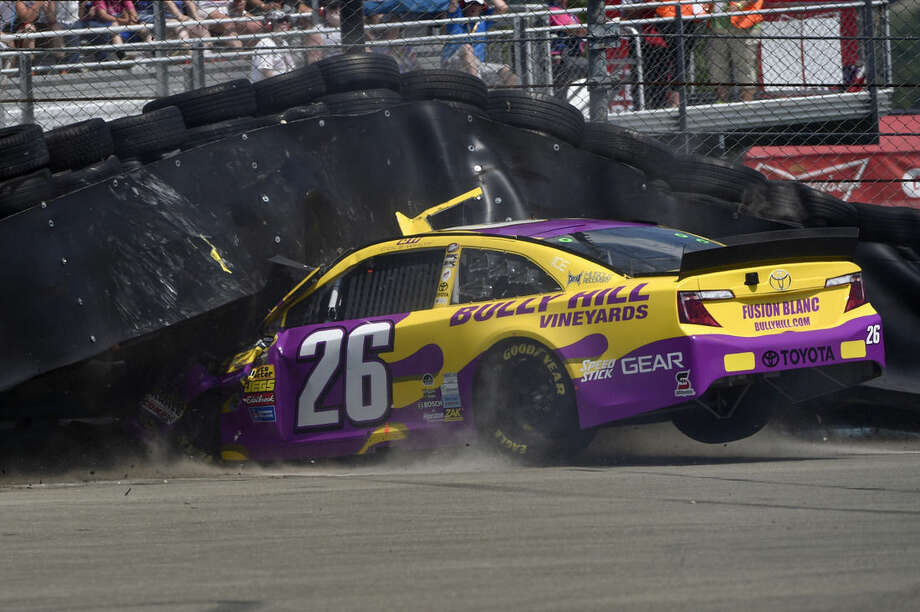 Cole Whitt (26) crashes into a tire wall off turn one during a NASCAR Sprint Cup Series auto race at Watkins Glen International, Sunday, Aug. 10, 2014, in Watkins Glen N.Y. (AP Photo/Derik Hamilton)