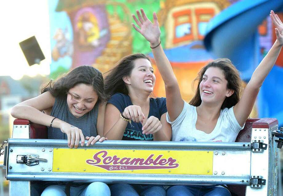 Hour Photo/Alex von Kleydorff Hanging on in The Scrambler Xuan Kusek, Rachel Delucia and Krsitina Casubolo enjoy the rides at The Norwalk Seaport Association Oyster Festival on Friday night