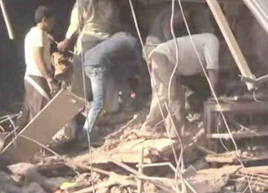 In this frame grab from video, people help clear debris at the scene after an explosion at a restaurant, Saturday, Sept. 12, 2015, in Petlawad, India. More than 80 people were killed when a cooking gas cylinder exploded and triggered a second blast of mine detonators stored illegally nearby, police said. (AP Photo/AP video)