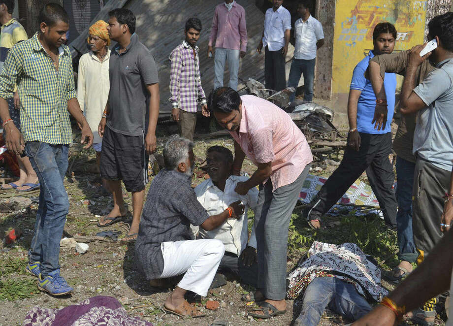 An injured man, whose relatives were killed, cries at the site of an explosion, with bodies of the dead lying around him, in Petlawad, in the central Indian state of Madhya Pradesh, Saturday, Sept. 12, 2015. Dozens of people were killed at a restaurant in central India on Saturday when a cooking gas cylinder exploded and triggered a second blast of mine detonators stored illegally nearby, police said. (AP Photo/Manoj Jani)