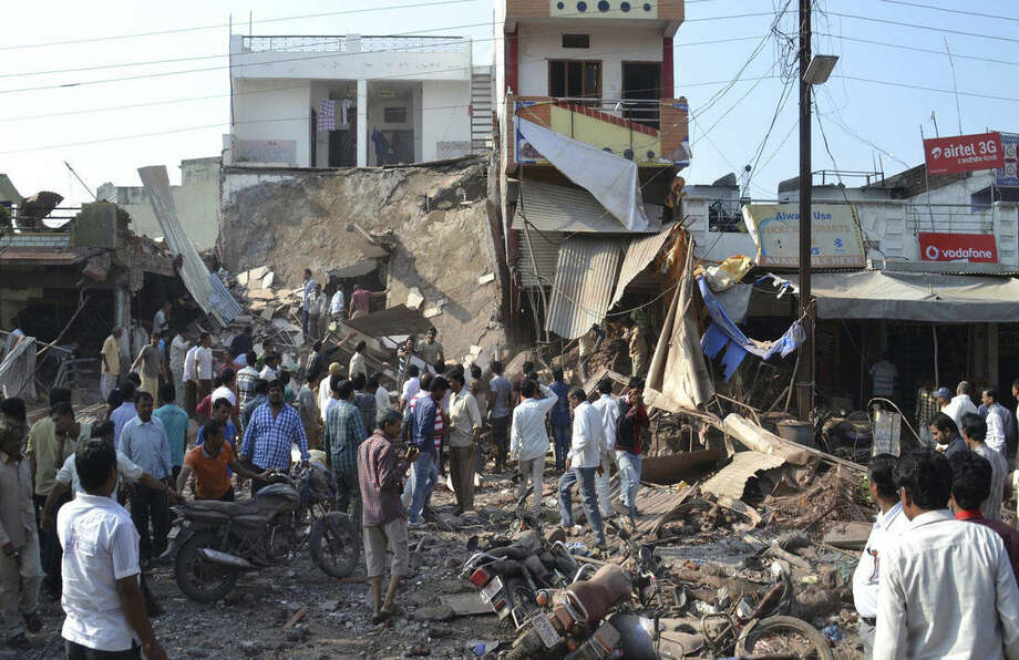 EDS NOTE: GRAPHIC CONTENT - A crowd gathers at the site of an explosion in Petlawad, in the central Indian state of Madhya Pradesh, Saturday, Sept. 12, 2015. Dozens of people were killed at a restaurant in central India on Saturday when a cooking gas cylinder exploded and triggered a second blast of mine detonators stored illegally nearby, police said. (AP Photo/Manoj Jani)