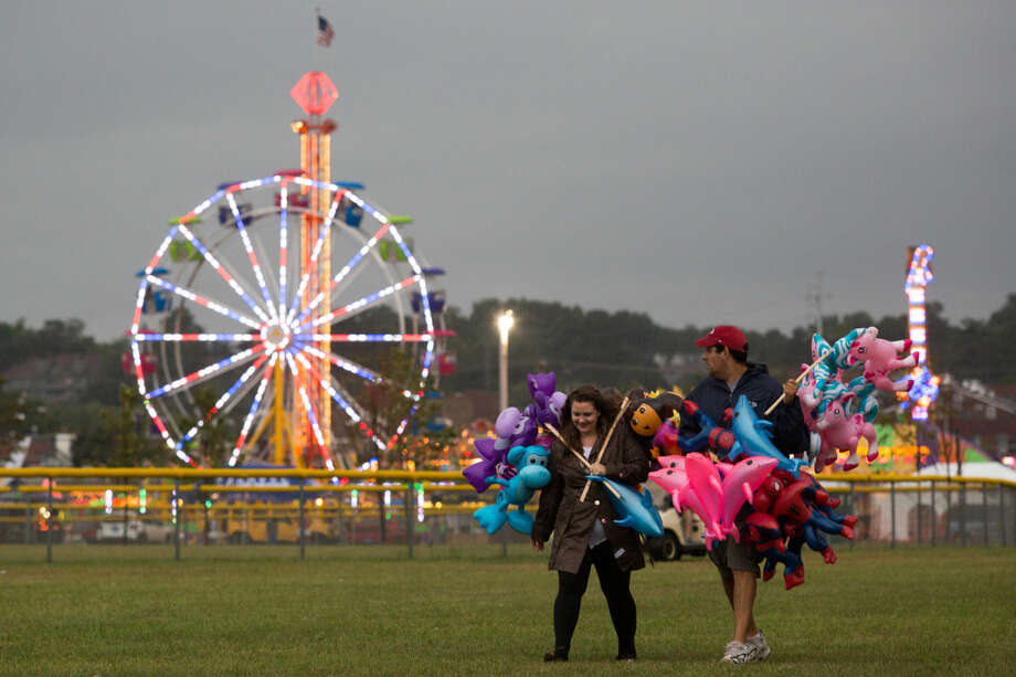 Hour photo/Chris Palermo. Vendors Bre Aurigema and Nick Dambrosia walk towards their car as the rain starts to fall at the Oyster Festival Saturday afternoon.