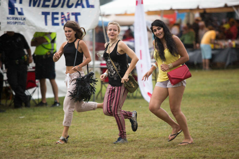 Hour photo/Chris Palermo. Festival goers run for shelter as the rain starts to come down at the Oyster Festival Saturday afternoon.
