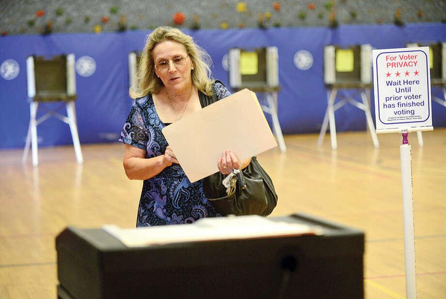 Hour photo / Erik Trautmann Karen Gasper casts her ballot at Marvin Elementary School during primary voting Tuesday in Norwalk.