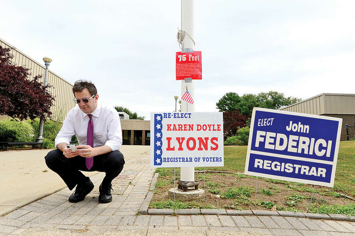Hour photo / Erik Trautmann State Representative Chris Perone ( D-137) checks messages while campaigning outside Marvin Elementary School during primary voting Tuesday in Norwalk.