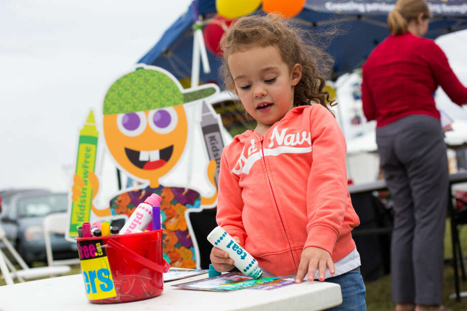 """Hour photo/Chris Palermo. Jianna Moirez, 3, colors at the """"Kids Draw Free"""" booth at the Oyster Festival Saturday afternoon."""