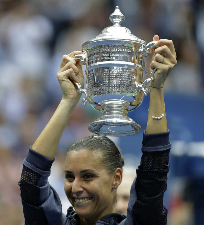 Flavia Pennetta, of Italy, holds up the championship trophy after beating Roberta Vinci, of Italy, in the women's championship match of the U.S. Open tennis tournament, Saturday, Sept. 12, 2015, in New York. (AP Photo/David Goldman)