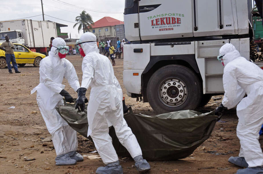 Health workers carry the body of a man suspected of dying from the Ebola virus and left in the street, as people watch in the background, in the capital city of Monrovia, Liberia, Tuesday, Aug. 12, 2014. The World Health Organization declared it's ethical to use untested drugs and vaccines in the ongoing Ebola outbreak in West Africa although the tiny supply of one experimental drug handed out to three people has been depleted and it could be many months until more is available. (AP Photo/Abbas Dulleh)