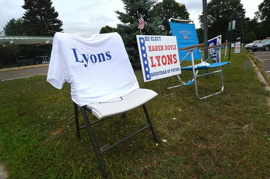 Hour Photo/Alex von Kleydorff While a volunteer steps away, a T Shirt helps to get the word out as a light rain starts to fall during voting in Norwalk on Tuesday.