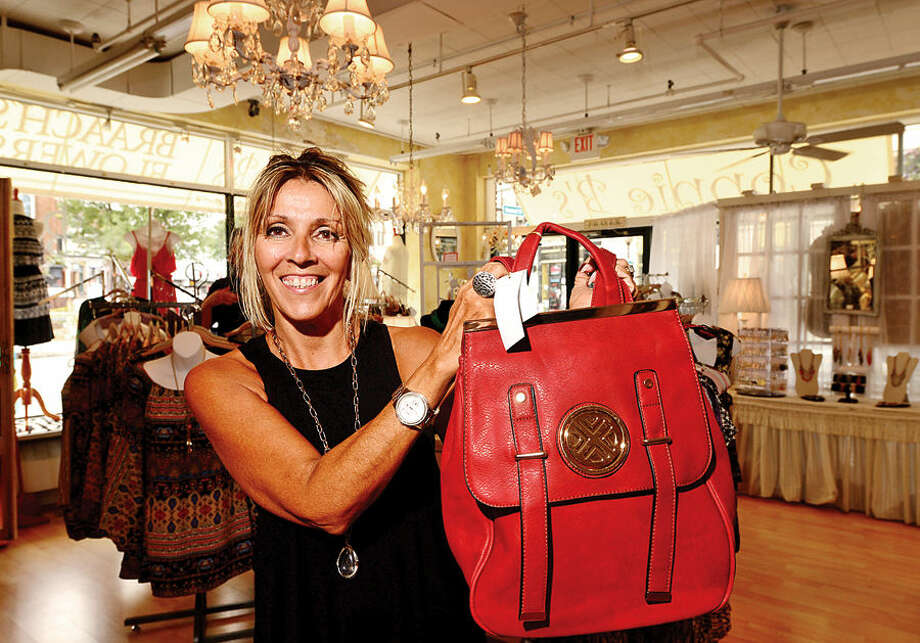 Hour photo / Erik Trautmann Connie B's sales associate Gina Till displays a purse backpack that is a hot item for back to school.