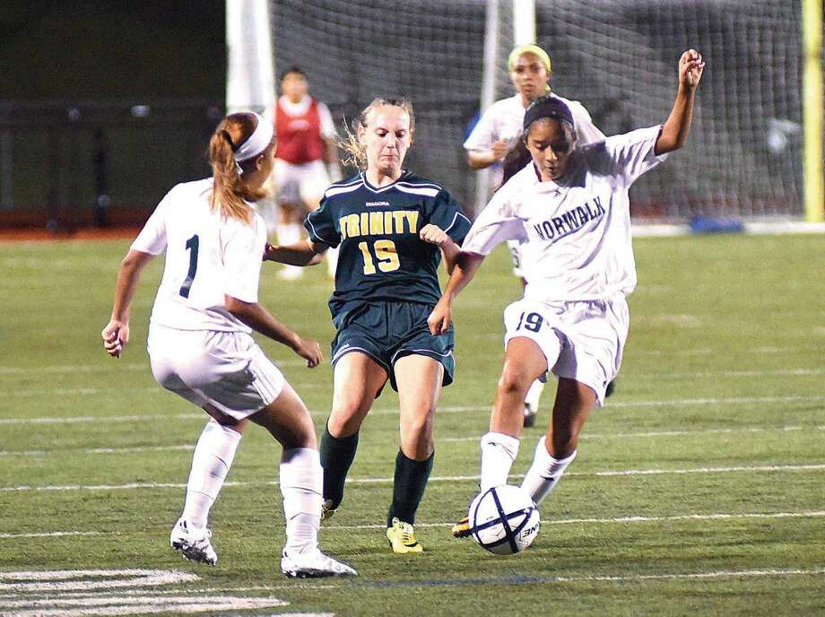 Hour photo/John Nash - Norwalk's Brianny Garcia (19) and Jayda Cruz (1) converge on the ball before Trinity Catholic's Keri Gallagher can get to it during Saturday's season-opening game at Testa Field in Norwalk.