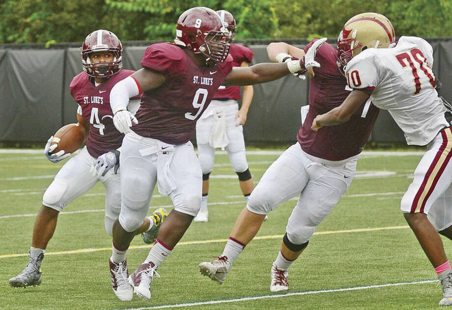 Hour photo/Erik TrautmannSt. Luke's fullback and Norwalk resident BJ Buckle (9) makes the lead block for running back Justin Brown as St Luke's School defeated St. Anthony's of New Jersey 41-35 in New Canaan Saturday.