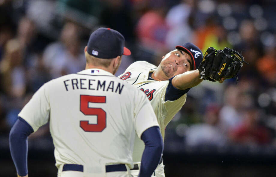 Atlanta Braves starting pitcher Williams Perez, right, fails to catch the ball after an infield pop fly hit by New York Mets' Travis d'Arnaud as first baseman Freddie Freeman (5) watches during the fourth inning of a baseball game, Saturday, Sept. 12, 2015, in Atlanta. (AP Photo/Jon Barash)