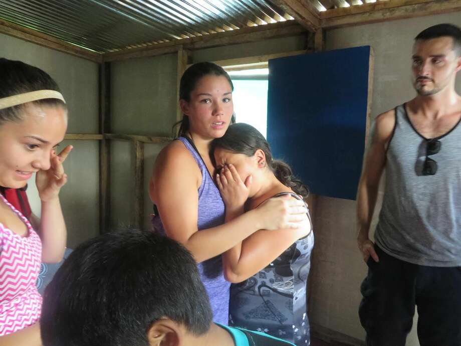 Contributed photo Team member Robyn comforts the mother of the family who the team built a house for.
