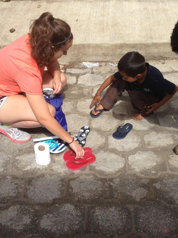Contributed photo Rev. Artie Kassimis's Nicolettedaughtergives shoes to a Guatemalan boy.