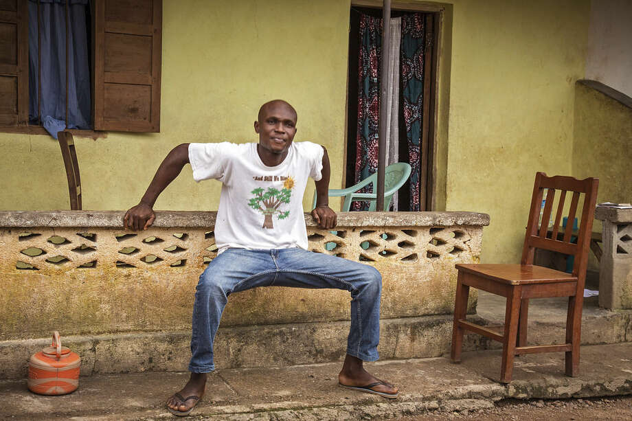 In this photo taken Monday, Aug. 11, 2014, Sulaiman Kemokai a Ebola virus survivor stretches in front of his house in the Heigbema Village in Kenema situated in the Eastern Province around 300km, (186 miles), from the capital city of Freetown in Kenema, Sierra Leone. In Sierra Leone, Sulaiman Kemokai, 20, was released from an Ebola treatment center on Sunday after spending 25-days in a ward there. He still feels stiffness in his joints but says he is gaining strength each day. (AP Photo/ Michael Duff)