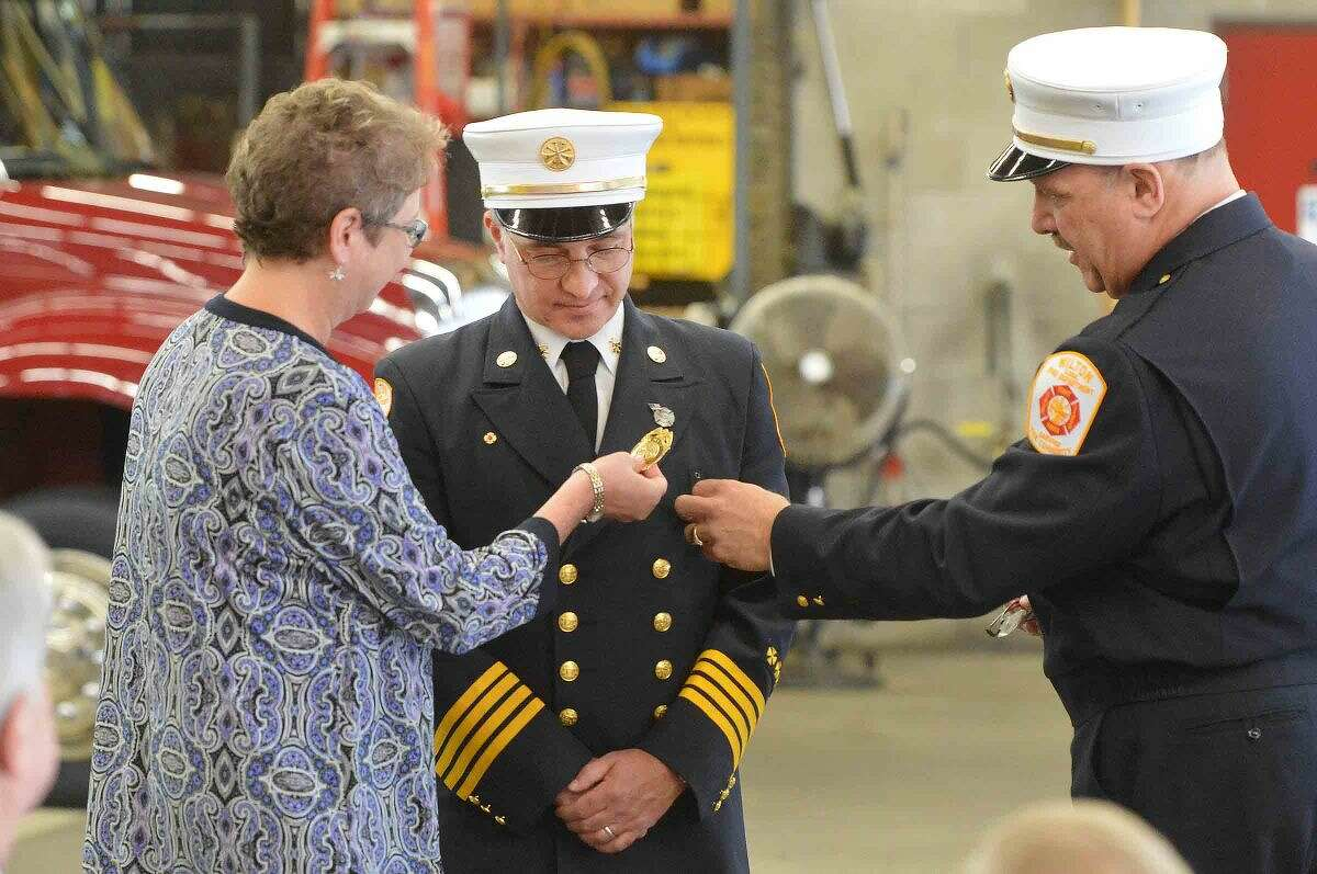 Fire Chief Ronald Kanterman shows Rocco Grosso's wife, Tamara, where to pin the shield as Grosso is sworn in as fire marshal at the Wilton Fire Department.