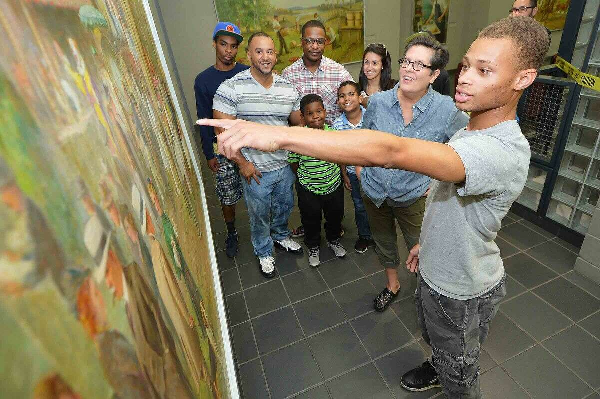 Hour Photo/Alex von Kleydorff 17yr old High Road School Senior Kyle Vigneault finds the details in one of the murals 'Danbury Fair' during a school tour of city hall with Art Commission Curator Melissa Slattery on Friday