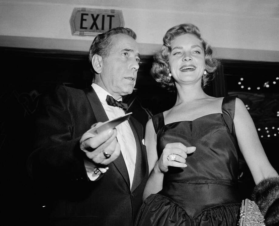 "This Oct. 12, 1955 file photo shows actors Humphrey Bogart, left, and his wife, Lauren Bacall at the premiere of ""The Desperate Hours,"" in Los Angeles. Bacall, the sultry-voiced actress and Humphrey Bogart's partner off and on the screen, died Tuesday, Aug. 12, 2014 in New York. She was 89."