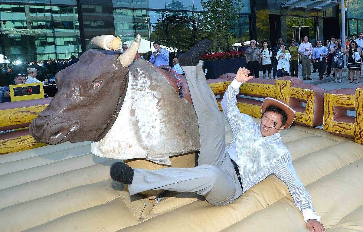 Hour Photo/Alex von Kleydorff Ryan Ruan lasts about 30 seconds with one hand on the mechanical bull at Building and Land Technology tennant appreciation party