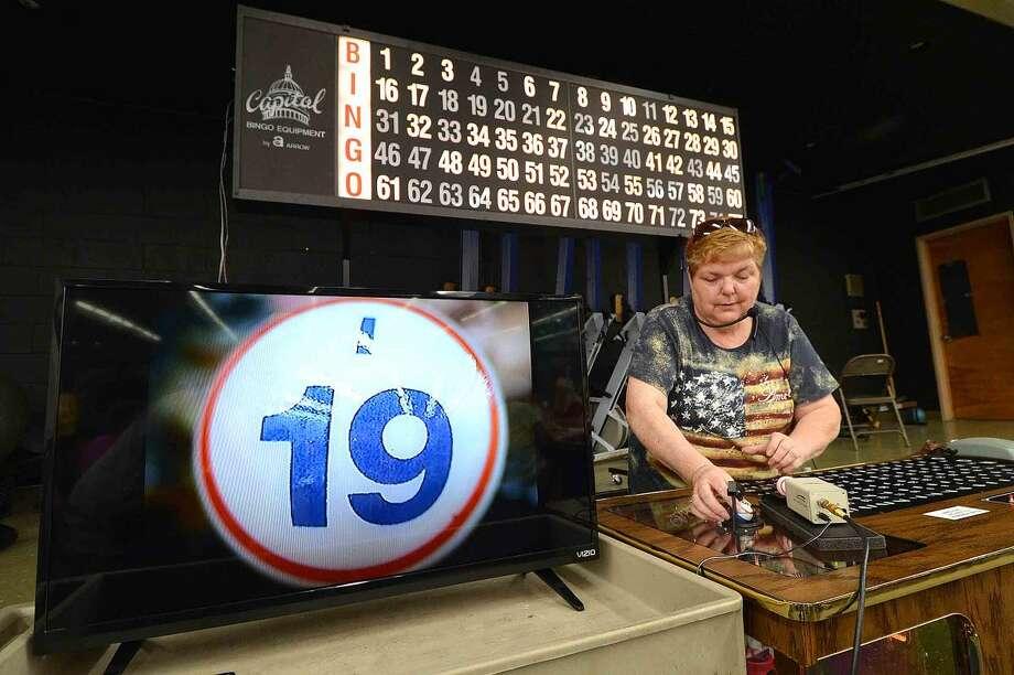 Hour Photo/Alex von Kleydorff Caller Dori Bolduc pulls up the numbers at Thursday Night Bingo at The Norwalk senior Center