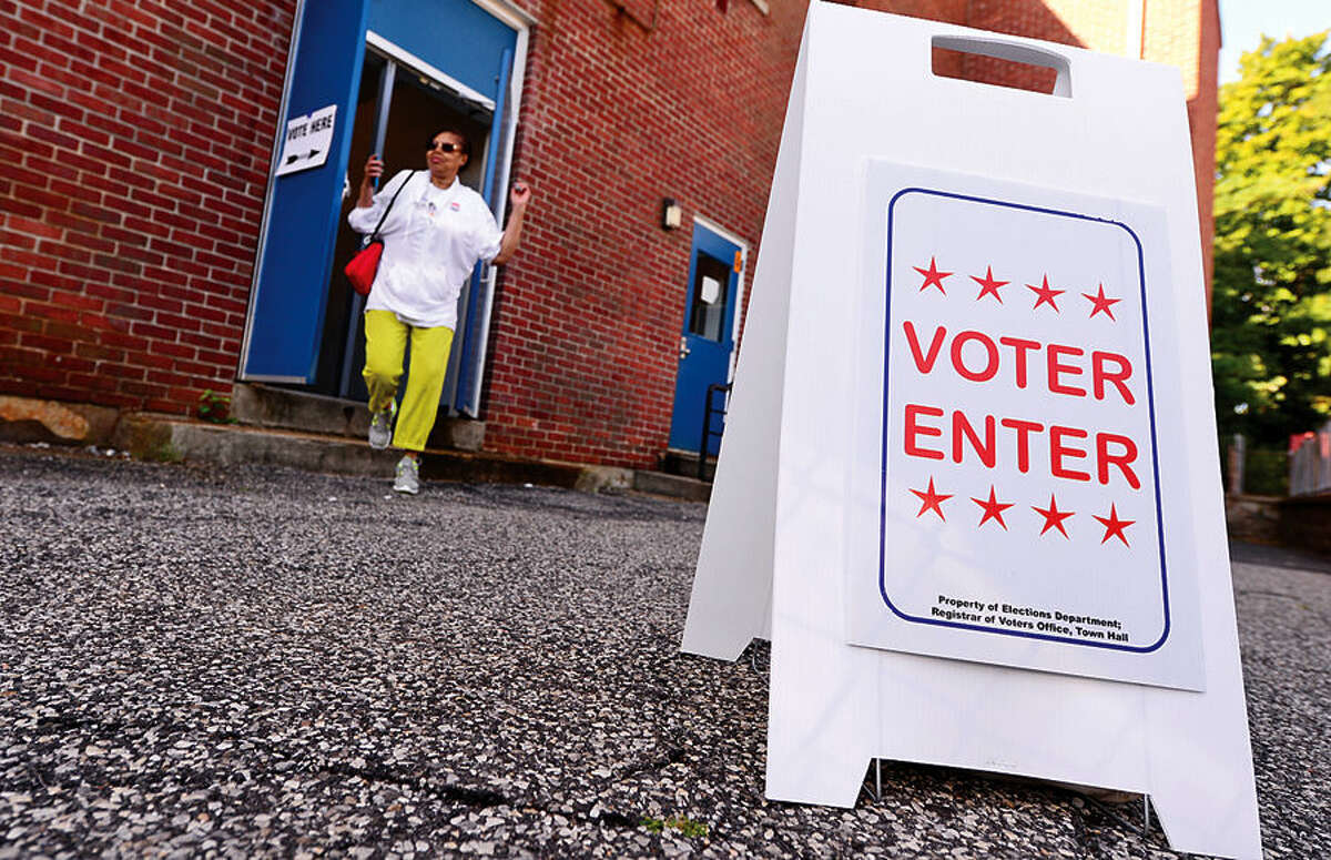 Hour photo / Erik Trautmann Voter Lilina Williams exits the polling station after casting her ballot in the democratic primary election at Columbus Magnet School Wednesday morning.