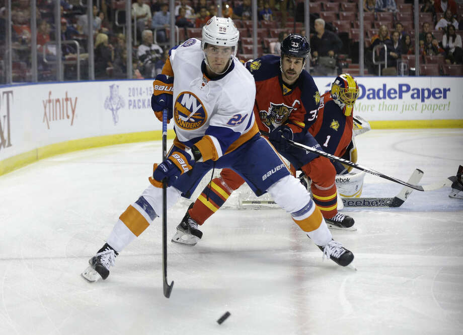 FILE - In this Friday, Nov. 14, 2014 file photo, New York Islanders center Brock Nelson (29) and Florida Panthers defenseman Willie Mitchell (33) go for the puck in the first period of an NHL hockey game in Sunrise, Fla. The New York Islanders re-signed center Brock Nelson to a three-contract Wednesday, Sept. 16, 2015. (AP Photo/Lynne Sladky, File)