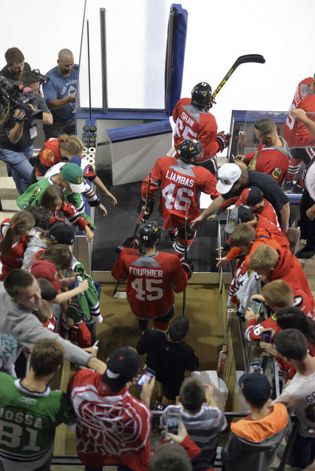 Chicago Blackhawks step into the ice through fans during NHL hockey training camp at the Compton Family Ice Center on the campus of the University of Notre Dame in South Bend, Ind., Friday, Sept. 18, 2015. (AP Photo/Joe Raymond)