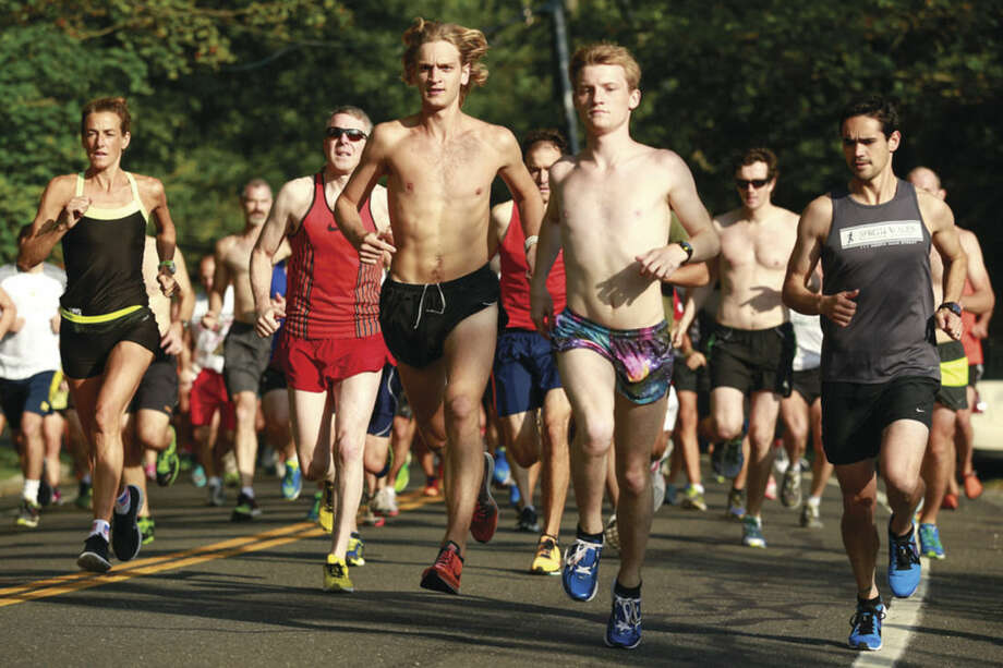 Hour photo/Chris PalermoRunners begin the Westport Road Runners 8.43-mile road race at Burying Beach in the Greens Farms section of Westport on Saturday morning.