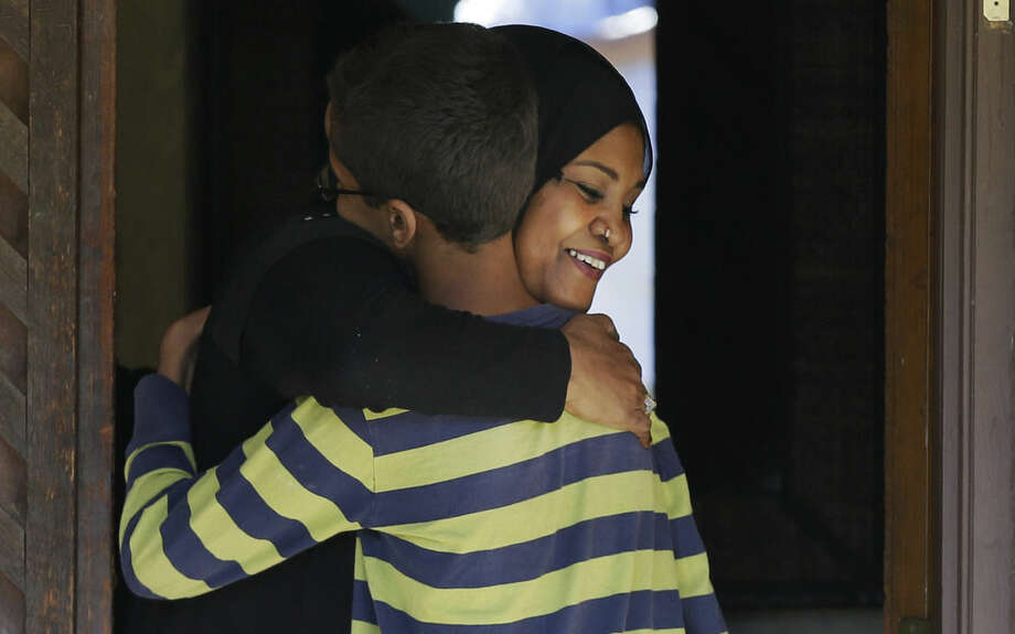 Ahmed Mohamed, 14, gets a hug when he arrives at his family's home in Irving, Texas, Thursday, Sept. 17, 2015. Ahmed was arrested Monday at his school after a teacher thought a homemade clock he built was a bomb. He remains suspended and said he will not return to classes at MacArthur High School. (AP Photo/LM Otero)