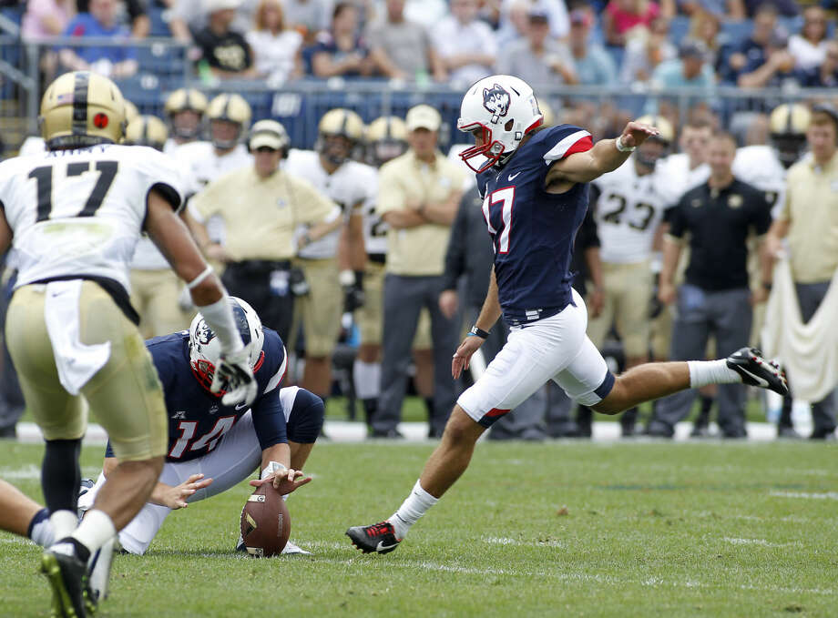 Connecticut place kicker Bobby Puyol kicks a field goal as quarterback Tim Boyle (14) holds for him during the second quarter of an NCAA college football game against Army at Pratt & Whitney Stadium at Rentschler Field, Saturday, Sept. 12, 2015, in East Hartford, Conn. Connecticut defeated Army 22-17. (AP Photo/Stew Milne)