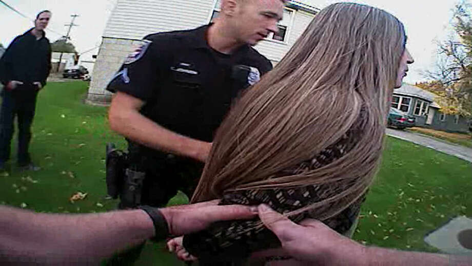 In this image from video provided by the Spokane Police Department police body camera video, police officers arrest a mentally ill woman in October 2014. The use of police body cameras is spreading to keep officers honest about using force against citizens. But how and when the public gets to see the footage is up for debate. (Spokane Police Department via AP)
