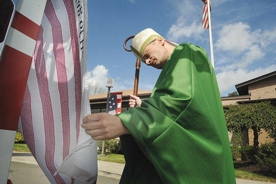 Bishop Frank J. Caggiano looks at the Flag of Heroes Sunday on Norwalk Fire Truck Number 1 in front of St. Matthew Church where the annual Diocesan Blue Mass in honor of police, fire and rescue workers. Hour photo/Matthew Vinci