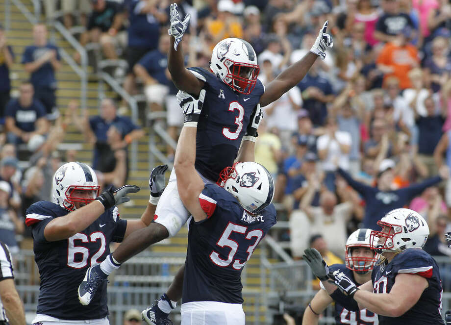 Connecticut running back Ron Johnson (3) is lifted in the air by offensive lineman Andreas Knappe after scoring a touchdown during the third quarter of an NCAA college football game against Army at Rentschler Field, Saturday, Sept. 12, 2015, in East Hartford, Conn. (AP Photo/Stew Milne)