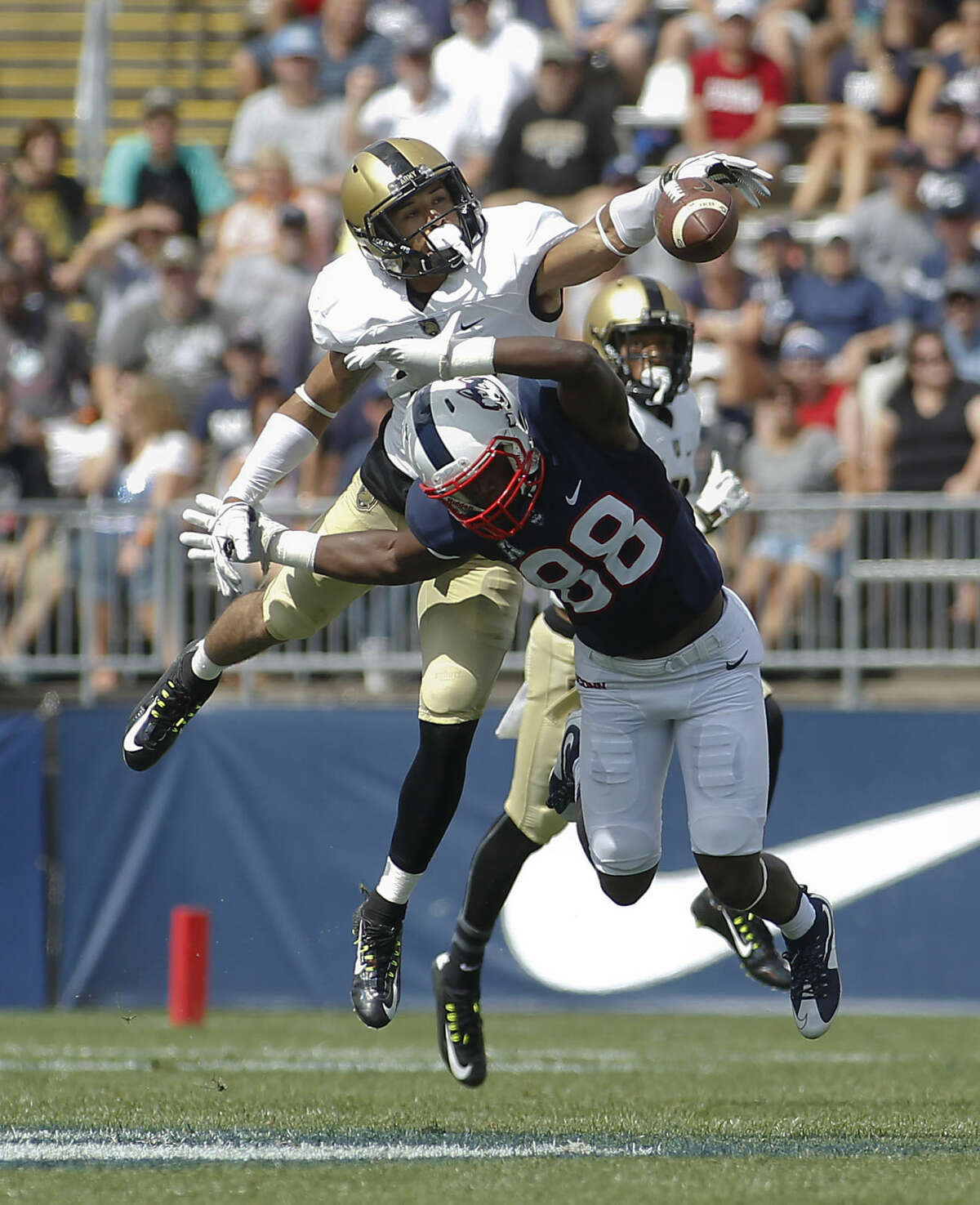 Army defensive back Steven Johnson, top, is called for pass interference on a pass intended for Connecticut wide receiver Hergy Mayala (88) during the second quarter of an NCAA college football game at Rentschler Field, Saturday, Sept. 12, 2015, in East Hartford, Conn. (AP Photo/Stew Milne)