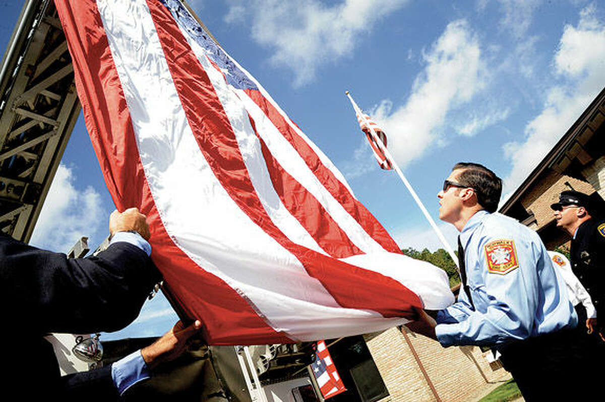Norwalk firefighter Brian Kaley helps raise the flag on fire truck number 1 at St. Matthew Church where the annual Diocesan Blue Mass in honor of police, fire and rescue workers. Hour photo/Matthew Vinci